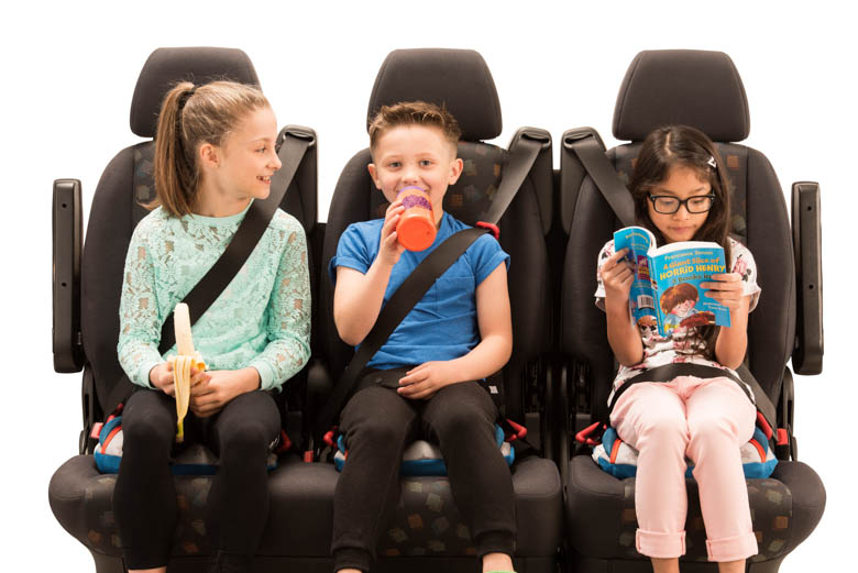 3 children sat on BubbleBum booster seats across the back seat of a car - USA design