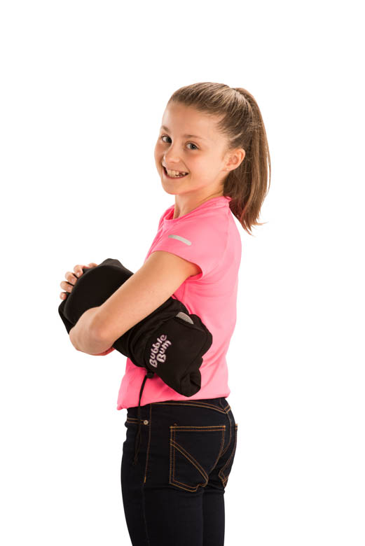 Girl holding black BubbleBum car booster seat under arm in carry bag