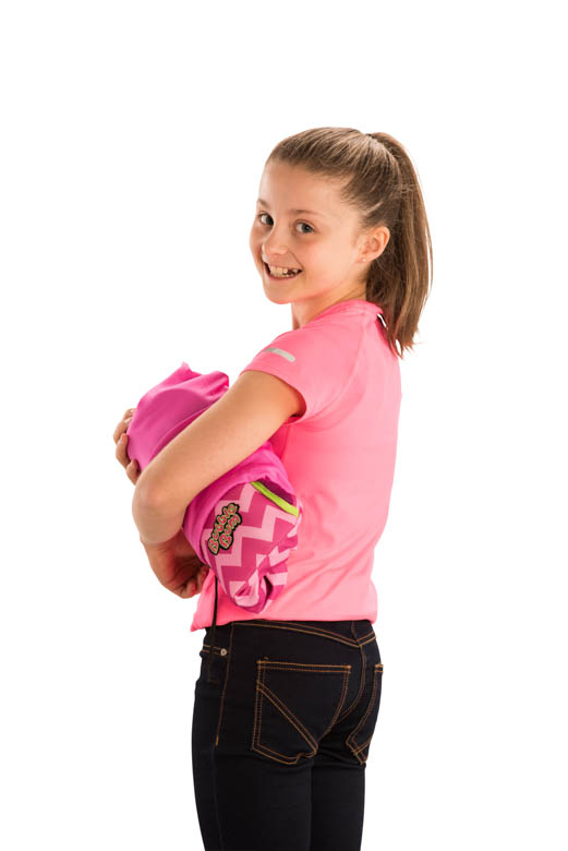 Girl holding pink BubbleBum car booster seat under arm in carry bag
